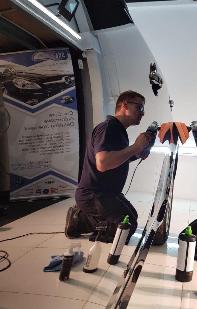 reflection of Jevgenijs machine polishing the side panel of a car